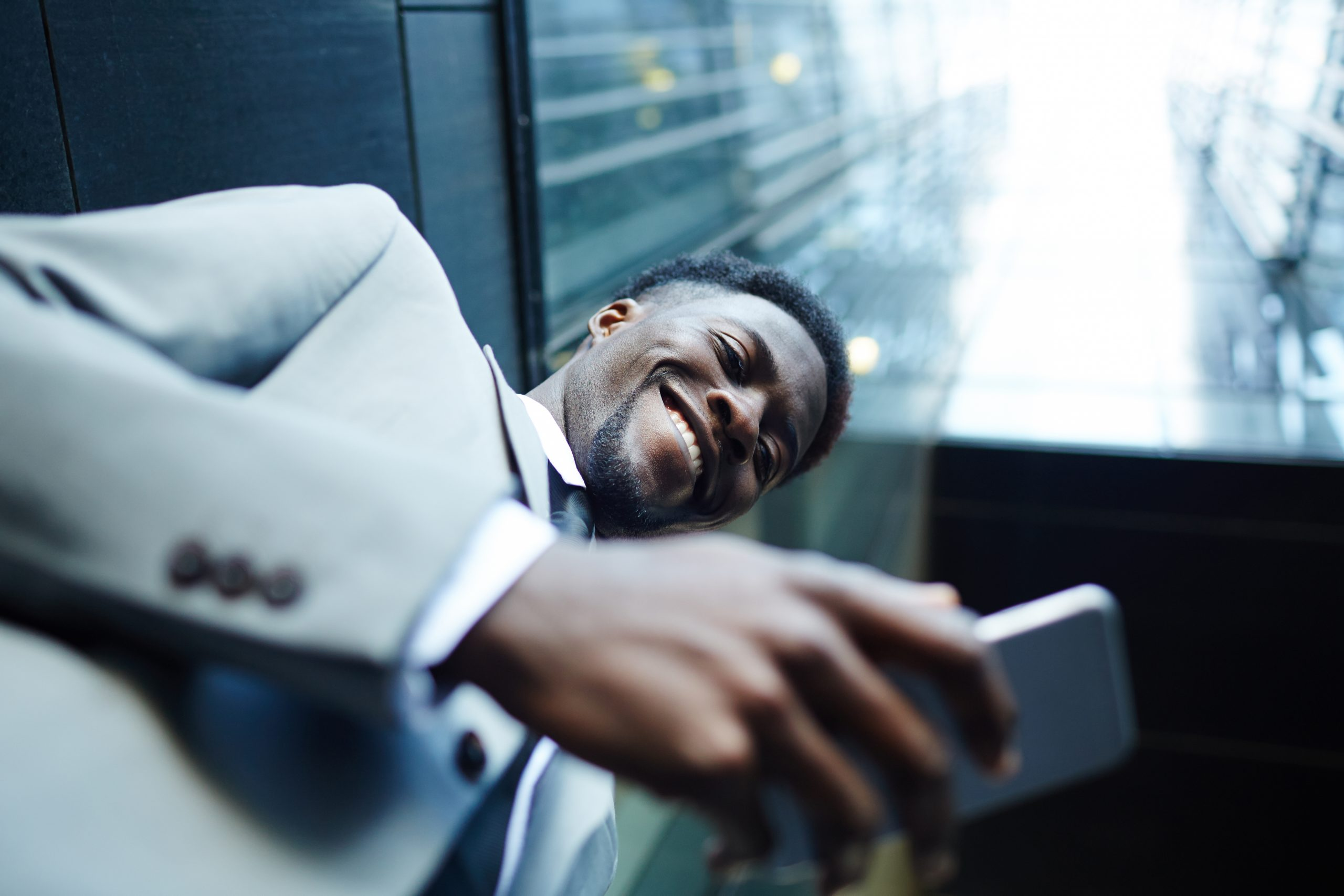 Businessman with mobile gadget texting in urban environment