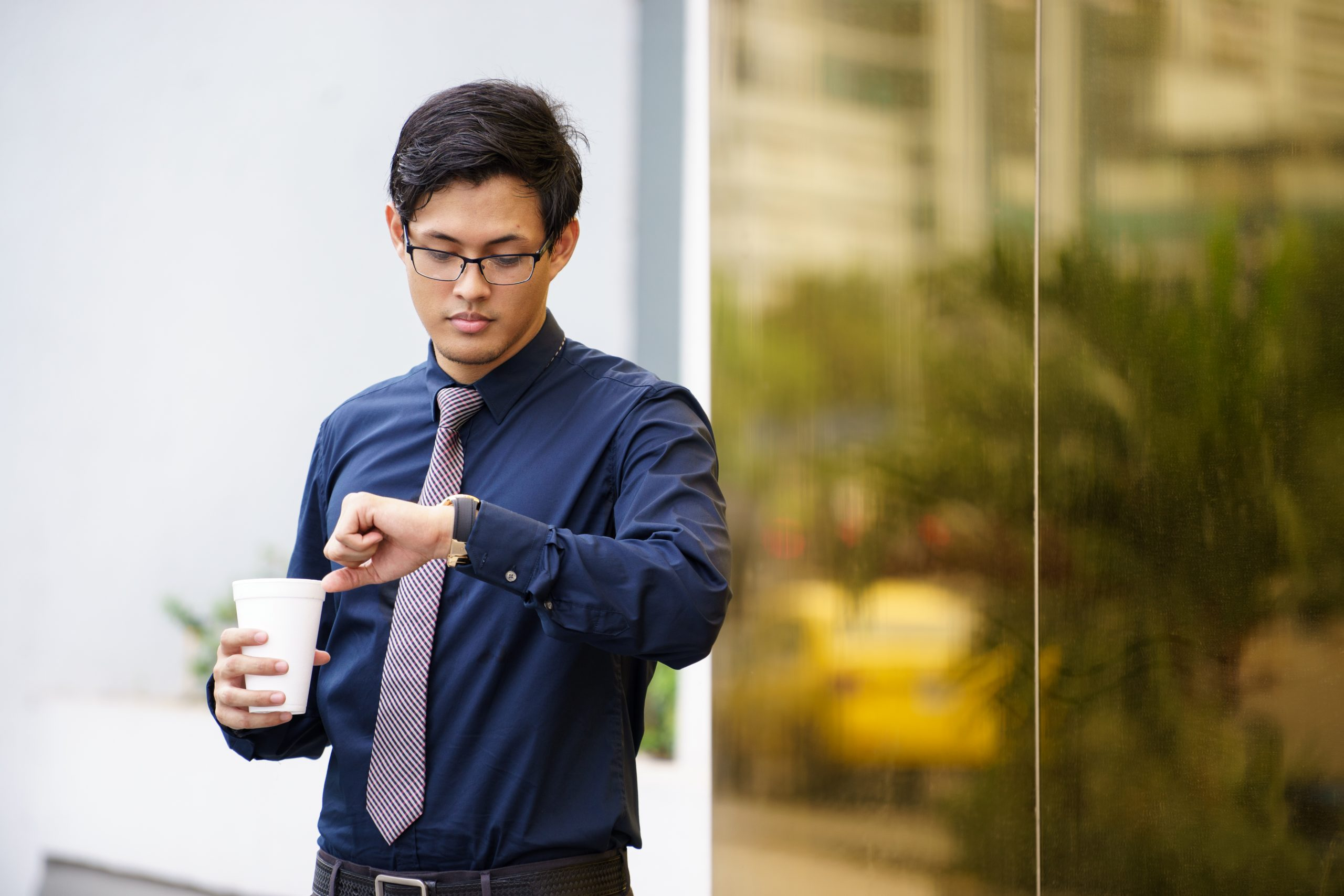 Portrait of chinese businessman standing near office building in Panama with coffee cup and checking the time on watch