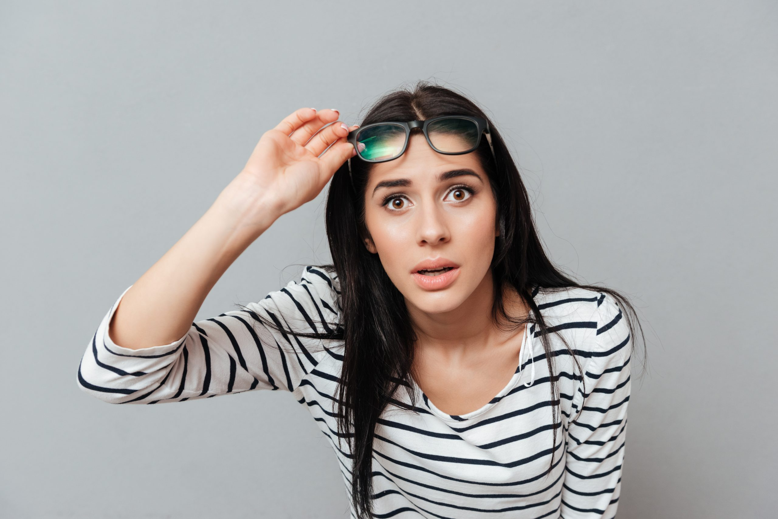 Young woman wearing eyeglasses shocked over grey background. Looking at camera.