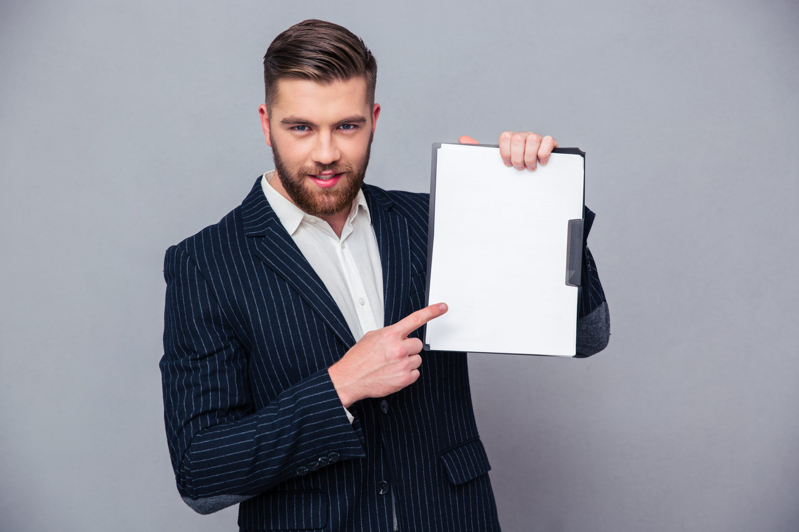 Portrait of a handsome businessman showing blank clipboard over gray background