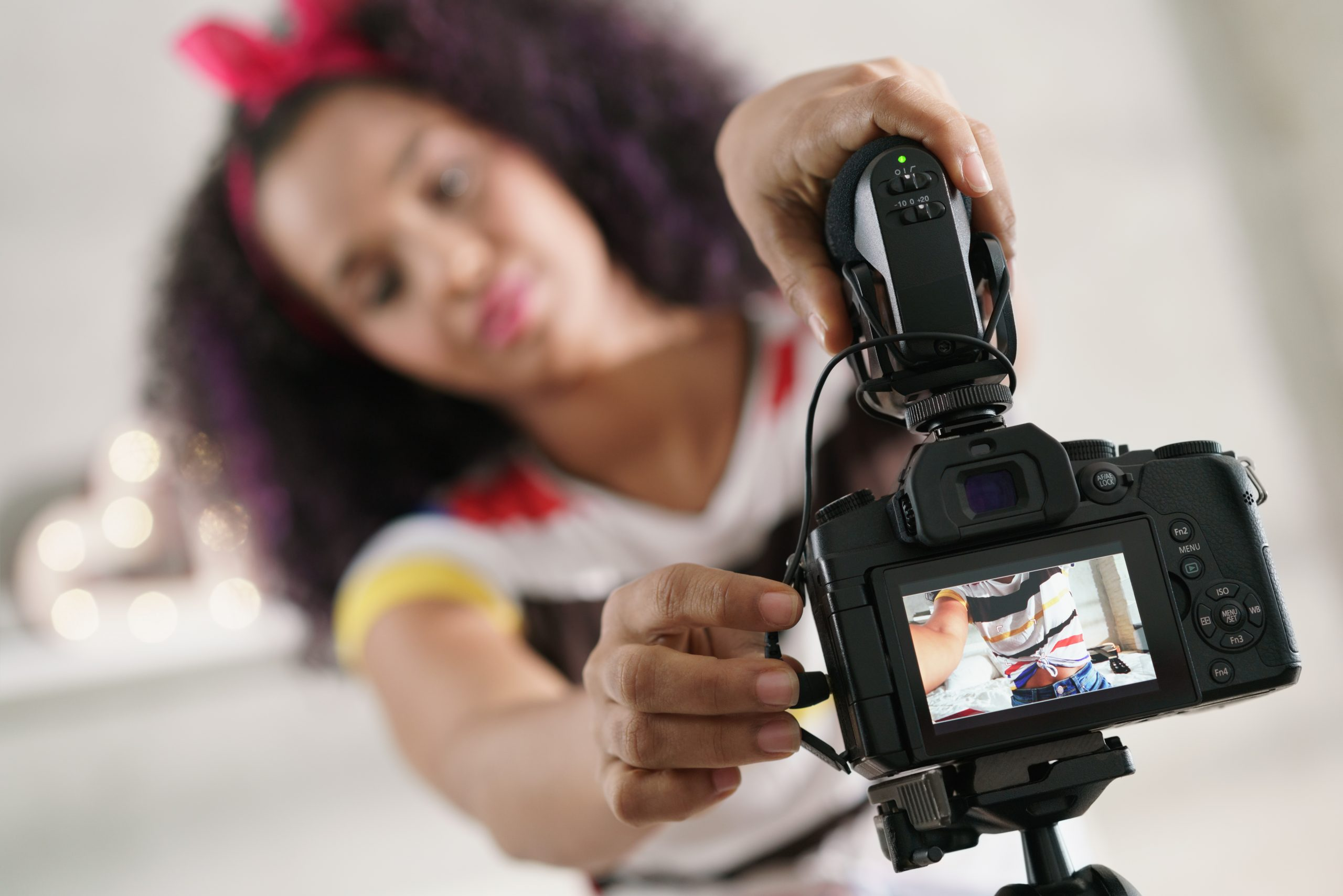 Black girl at home talking in front of camera, setting up microphone for recording Vlog at home. Young African American woman working as web influencer.